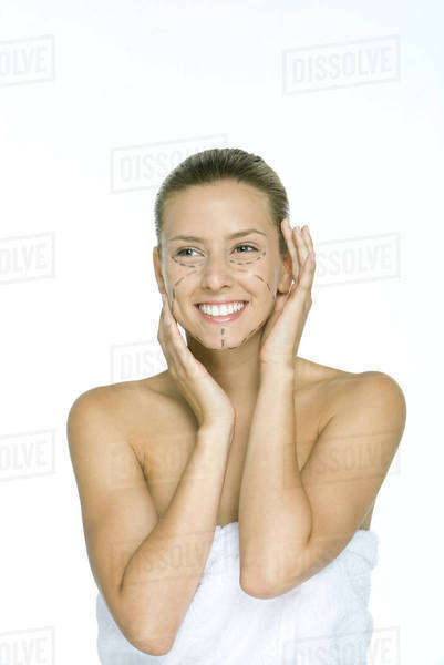 Woman with plastic surgery markings on face, holding head, smiling Royalty-free stock photo