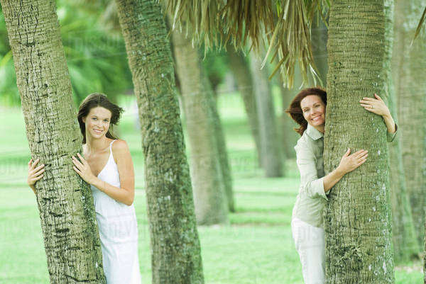 429da1139471c5 Mother and teen daughter hugging tree trunks