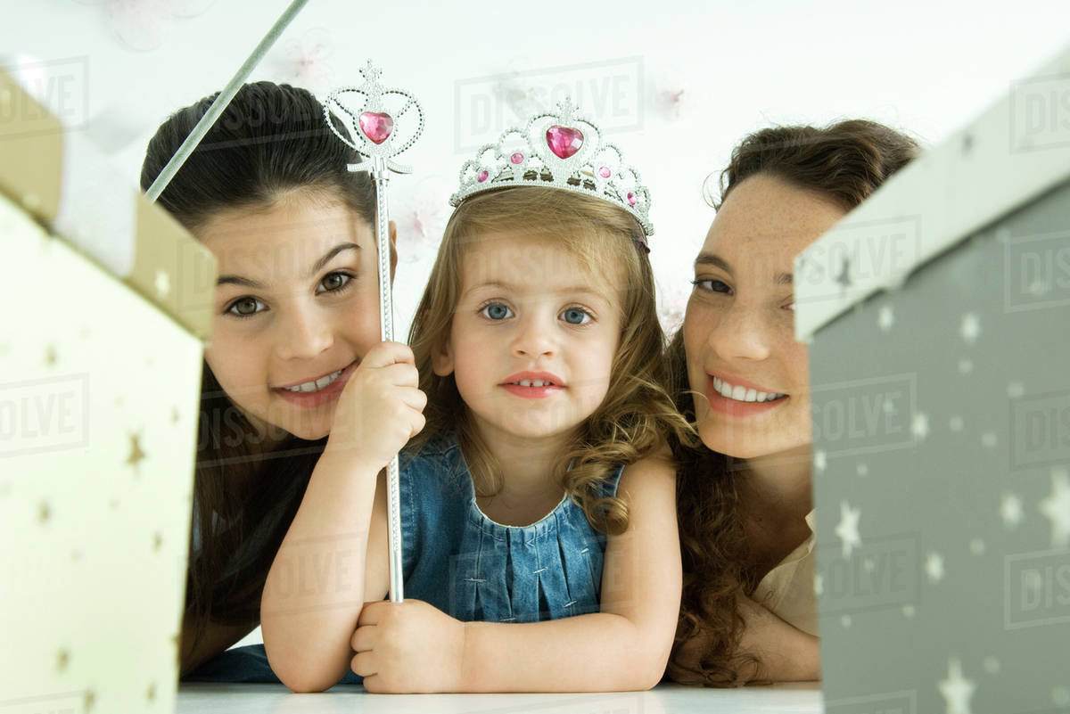 Little girl with mother and sister, dressed as princess, birthday gifts in foreground Royalty-free stock photo