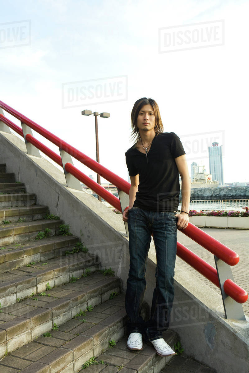 young japanese man standing on stairs leaning against railing