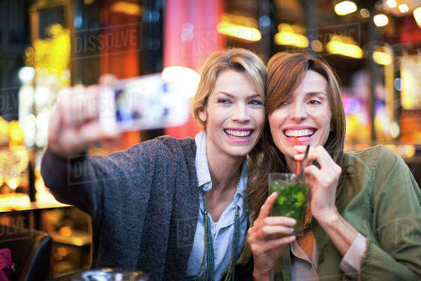 Women in bar taking self-portrait with photophone Royalty-free stock photo