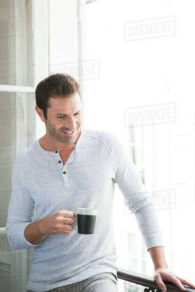 Man standing by window with mug in hand Royalty-free stock photo