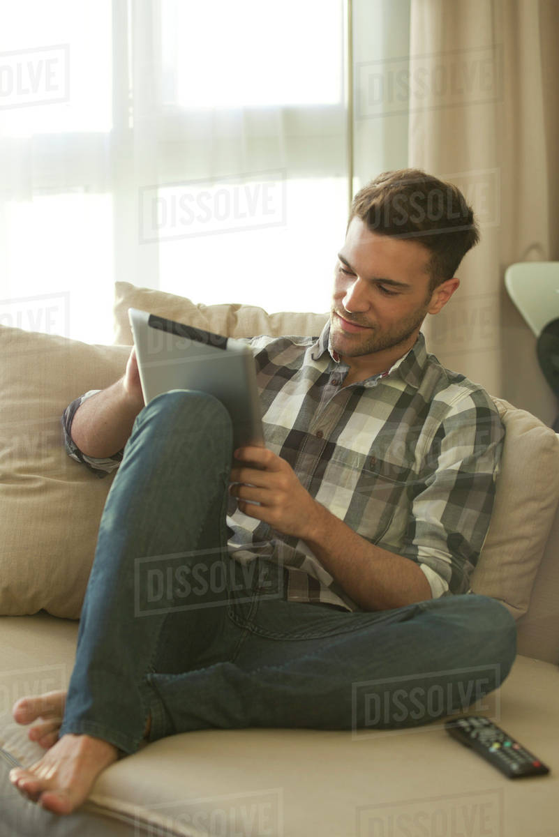 Young Man Relaxing On Couch At Home Using Digital Tablet