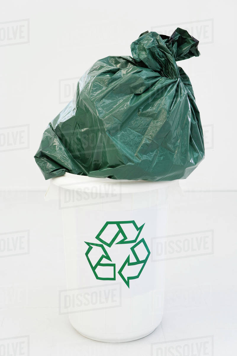 Excessively Large Garbage Bag Stuffed Partially Into Recycling Bin