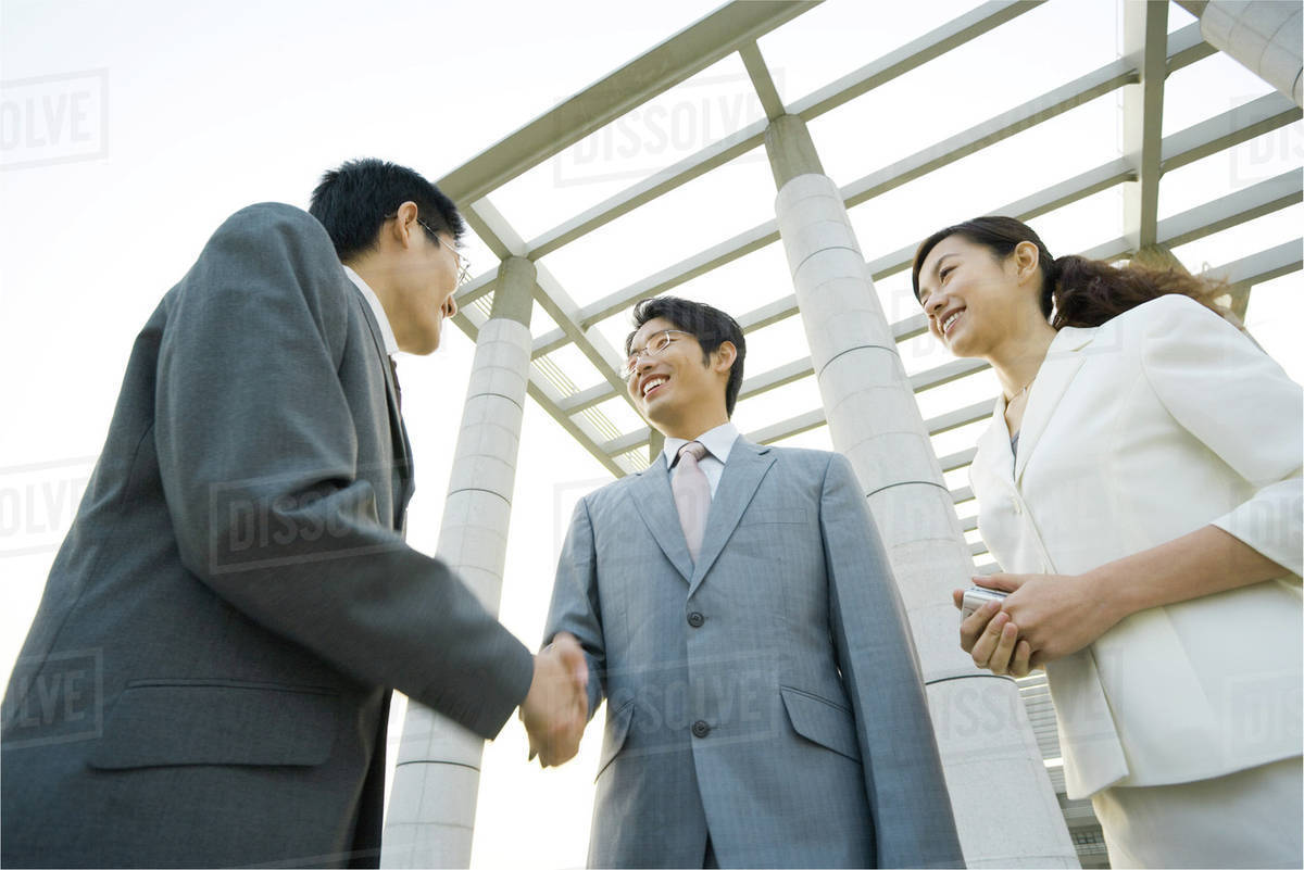 Two businessmen shaking hands while businesswoman stands nearby, low angle  view stock photo