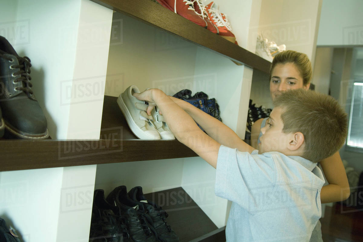Boy Putting Shoes On Shoe Rack While Mother Watches Stock Photo