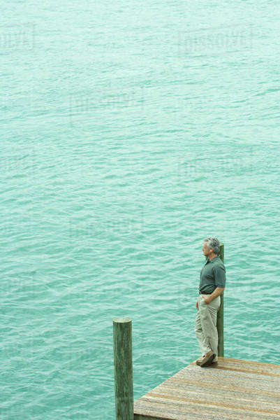 Man standing next to water listening to earphones, looking away, high angle view Royalty-free stock photo