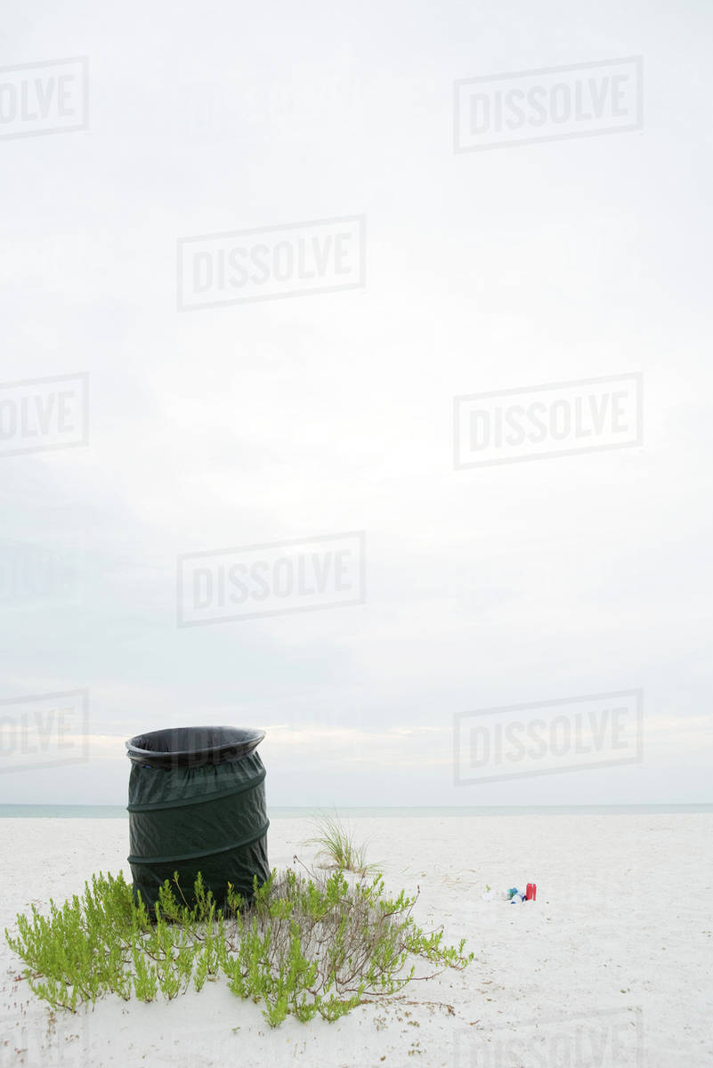 Garbage can on beach, litter lying on the ground nearby stock photo