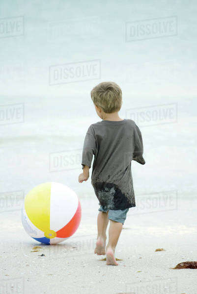 Little boy chasing beach ball at the beach, rear view Royalty-free stock photo