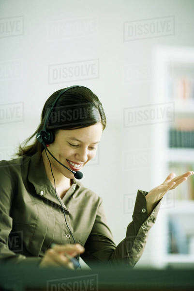 Woman wearing headset, gesturing with hand, looking down Royalty-free stock photo