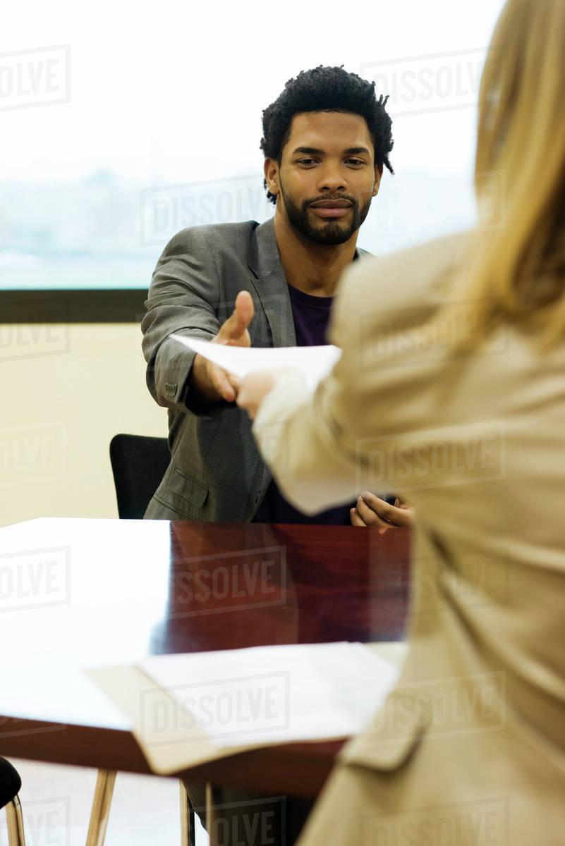 Man handing prospective employer his resume during job interview ...