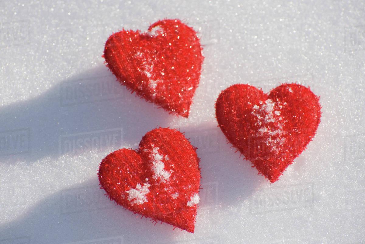 three heart shaped ornaments on snow stock photo dissolve