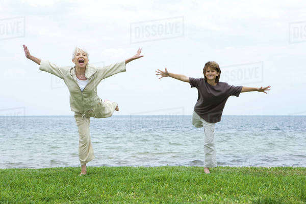 Grandmother and grandson standing on one leg, arms outstretched, both smiling at camera Royalty-free stock photo