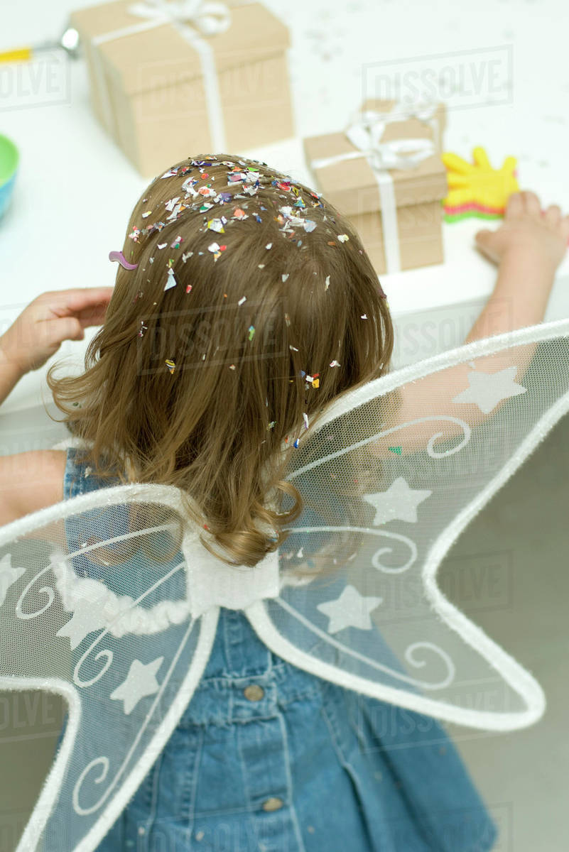Little girl wearing wings, confetti in her hair, rear view Royalty-free stock photo