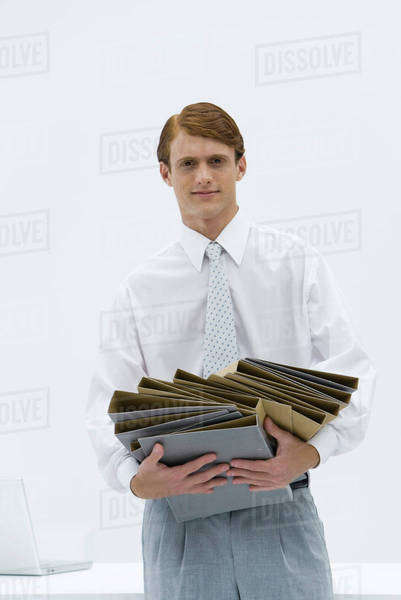 Professional man carrying a disorganized stack of binders, looking at camera Royalty-free stock photo