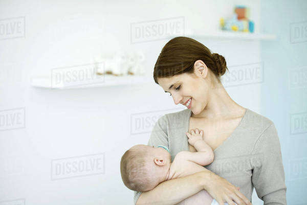 Mother in nursery, smiling down at baby in her arms Royalty-free stock photo