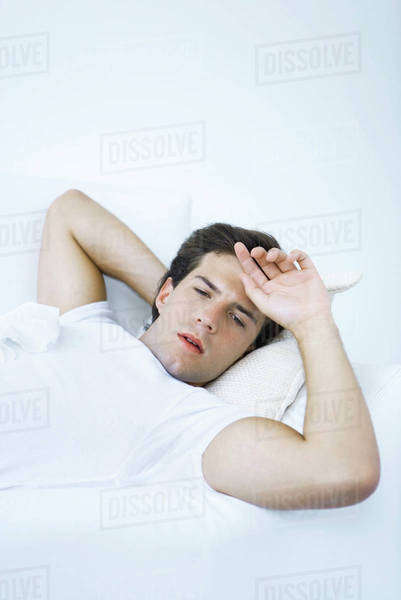 Man lying on sofa with tissue on his chest, hand on forehead Royalty-free stock photo