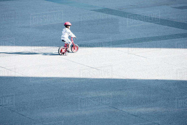 Child riding bicycle alone in public square Royalty-free stock photo