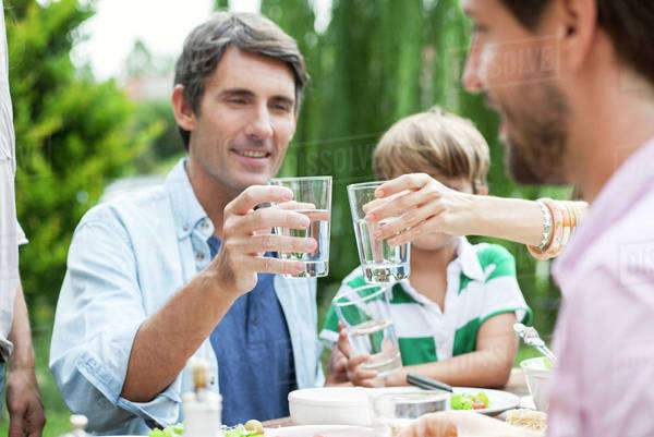 Family clinking glasses outdoors Royalty-free stock photo