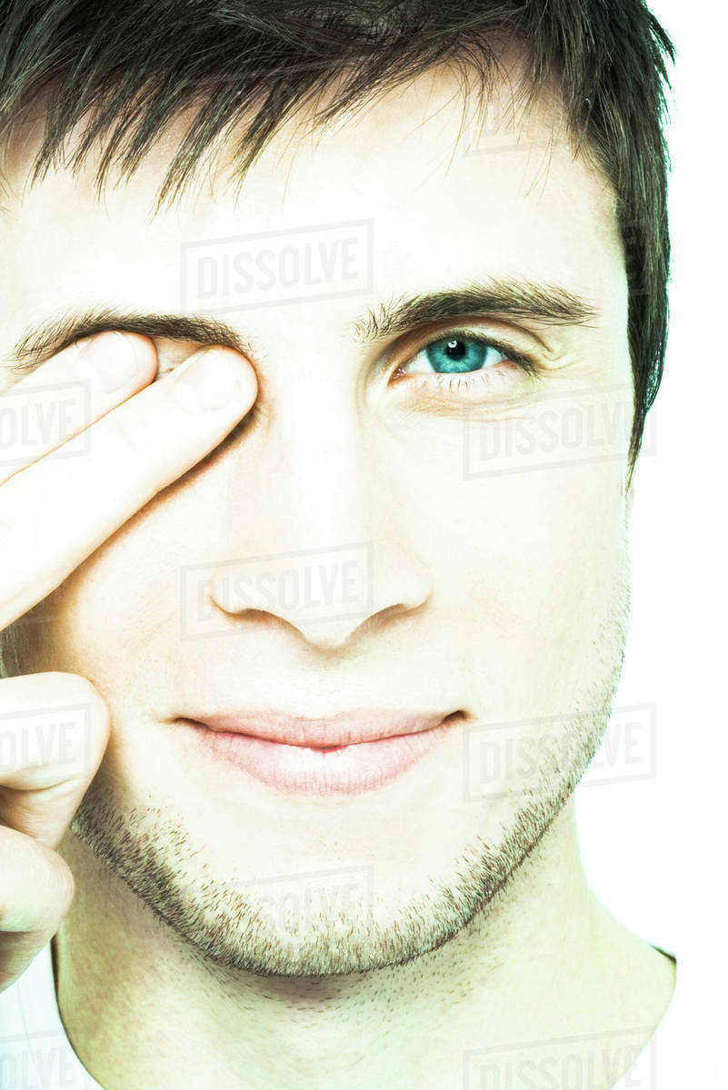 young man holding fingers over eye close up front view of face