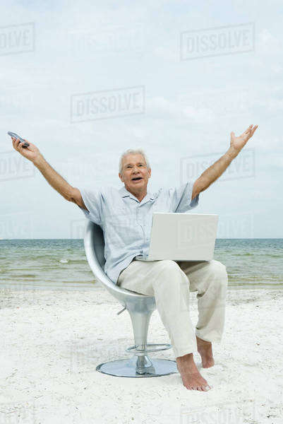 Senior man sitting on beach with laptop on lap, arms raised, shouting Royalty-free stock photo