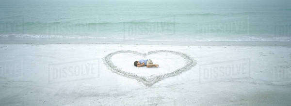 Child lying inside heart drawn on beach Royalty-free stock photo
