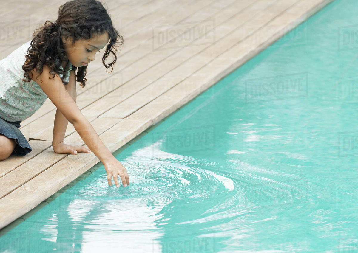 Little Girl Sitting By Edge Of Swimming Pool, Touching Surface Of Water - Stock Photo -1123