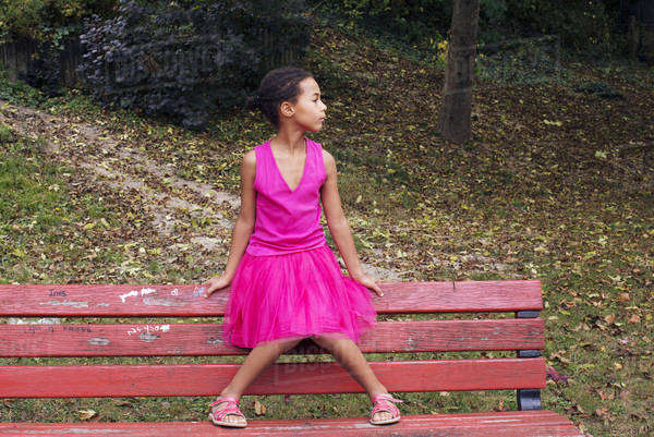 Girl sitting alone on park bench, looking away in thought Royalty-free stock photo
