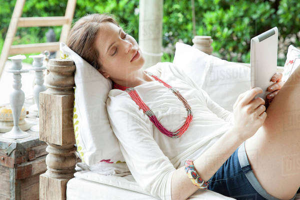 Young woman relaxing with digital tablet Royalty-free stock photo