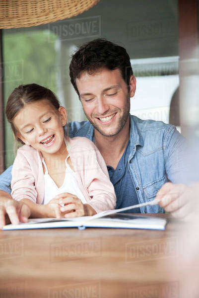 Father and daughter reading book together Royalty-free stock photo