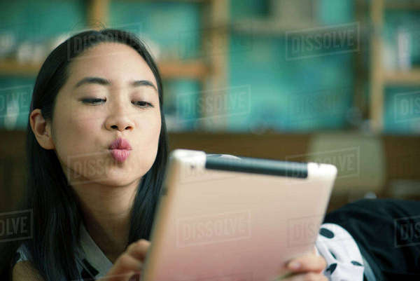 Young woman blowing kiss while video conferencing on digital tablet Royalty-free stock photo