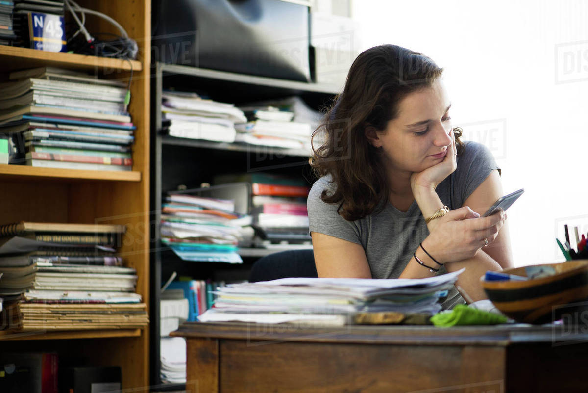 Office worker taking break to browse social media using smartphone Royalty-free stock photo
