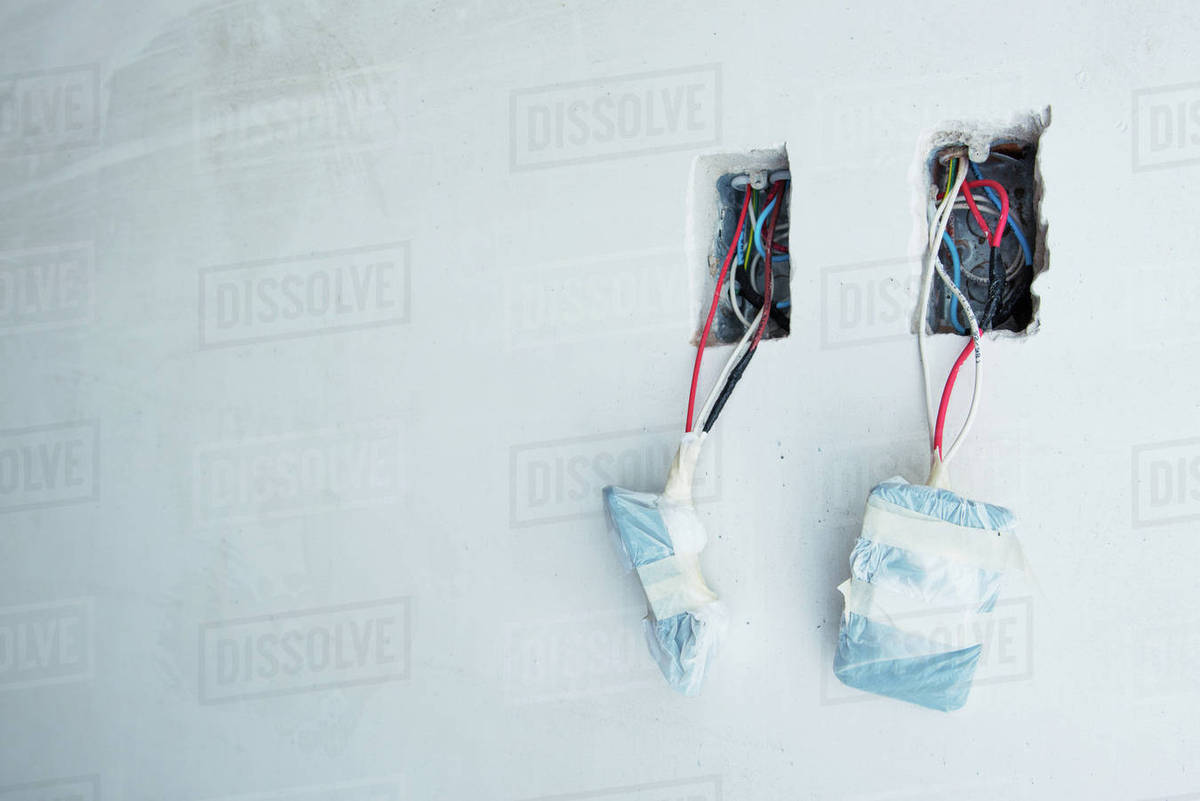 Electrical wires dangling from unfinished outlets in wall - Stock ...