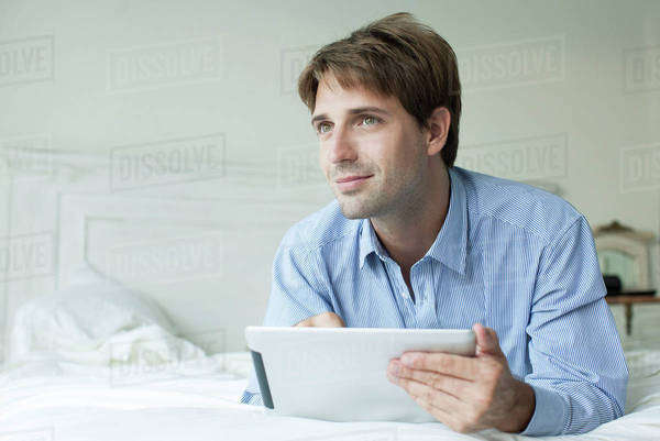 Man lying in bed using digital tablet, looking away with contemplative look Royalty-free stock photo