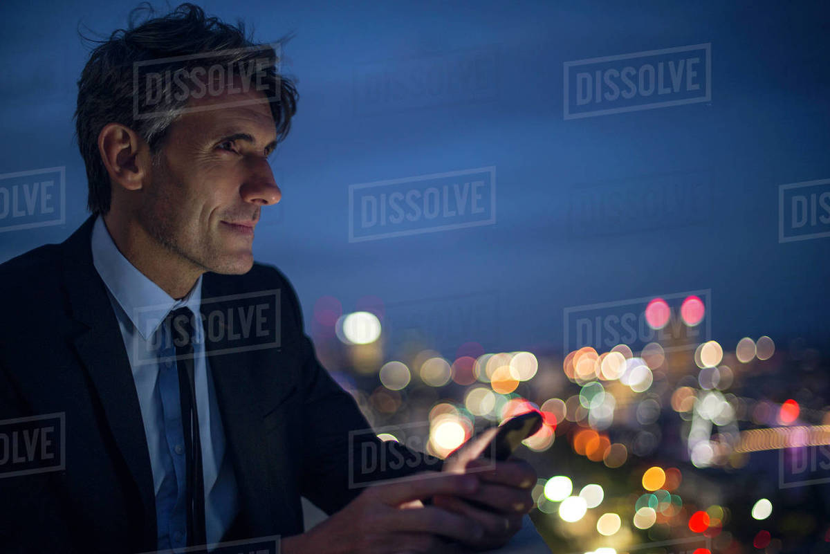 Businessman on high rise rooftop using mobile phone Royalty-free stock photo