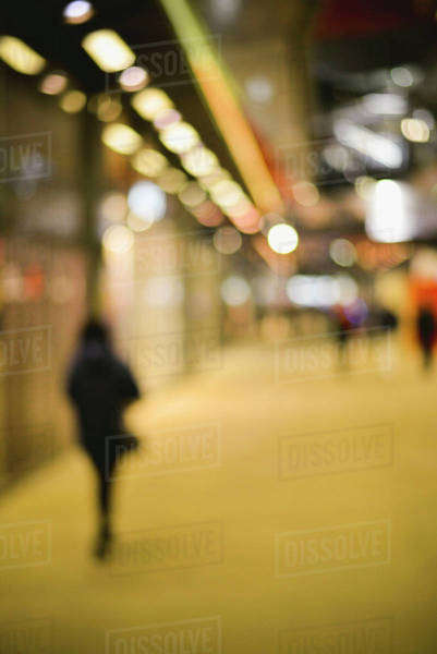 Pedestrian walking on sidewalk at night, defocused Royalty-free stock photo