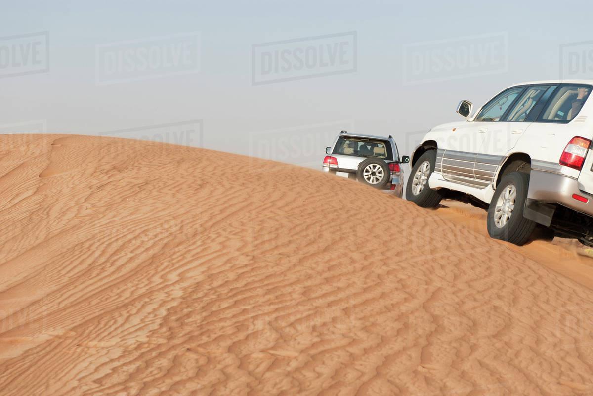 Sports Utility Vehicles Driving Up Desert Sand Dune D984 9 098
