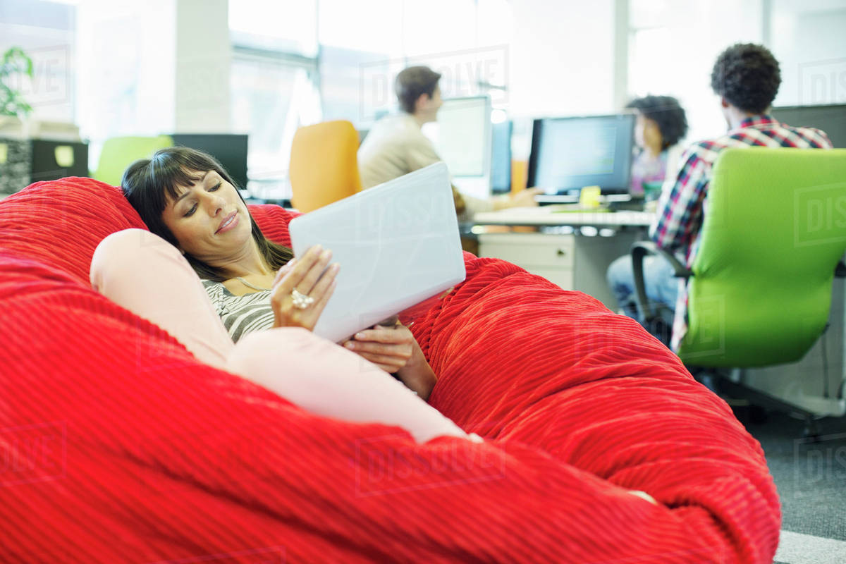 Businesswoman Using Laptop In Bean Bag Chair Office