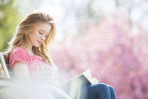 Woman reading book on park bench Royalty-free stock photo