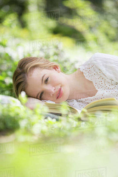 Woman relaxing in grass with book Royalty-free stock photo