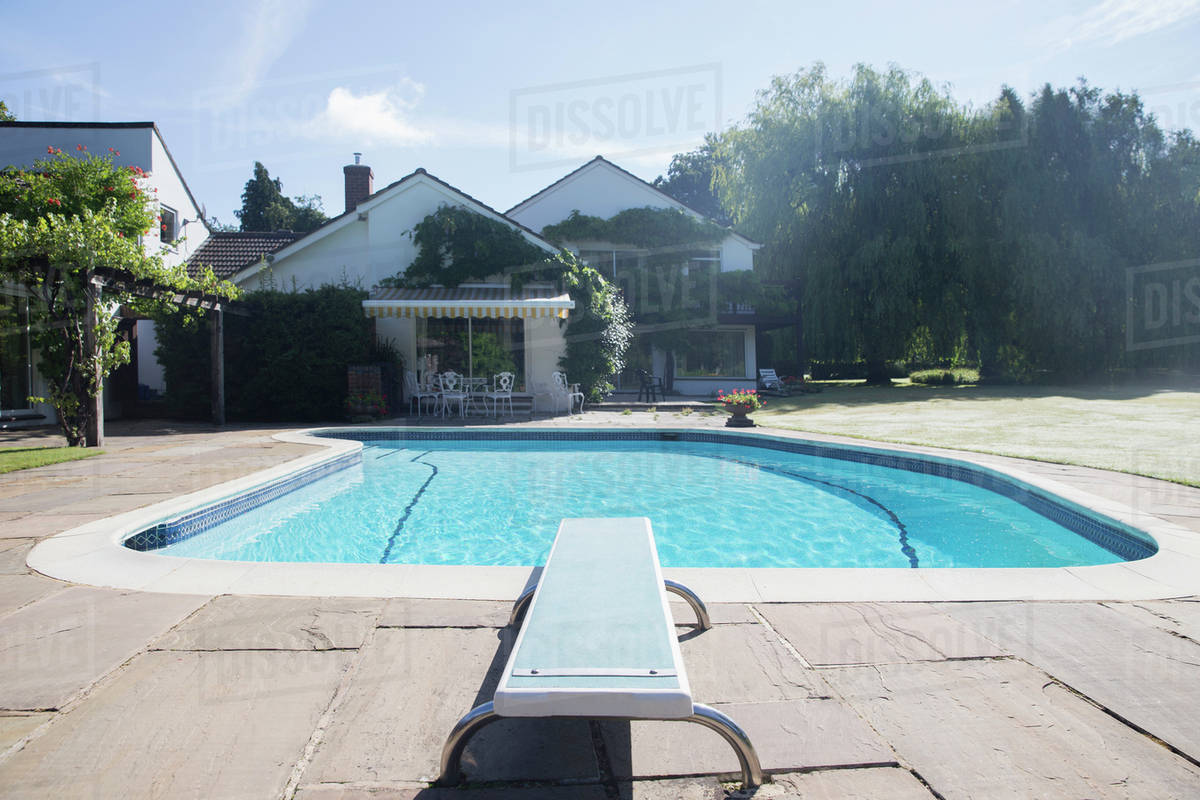 Diving board at the edge of swimming pool stock photo