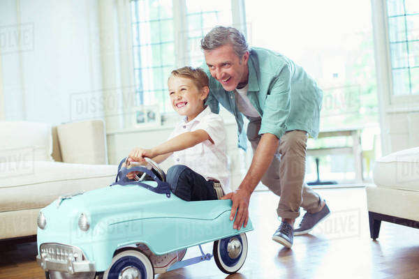 Father pushing son in toy car Royalty-free stock photo