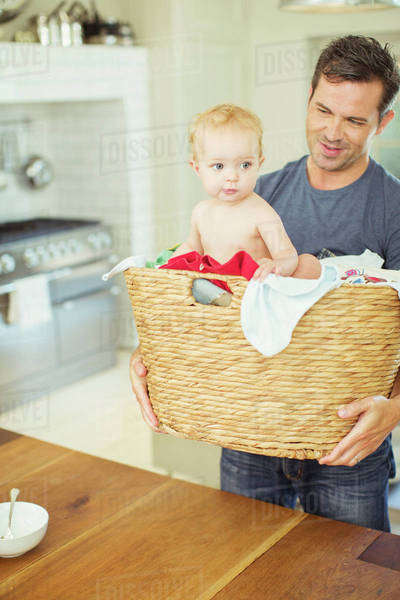 Father carrying baby in laundry basket Royalty-free stock photo