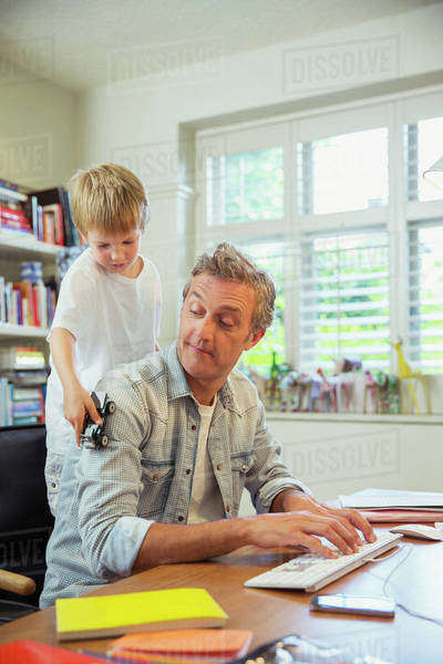Boy distracting father at work in home office Royalty-free stock photo