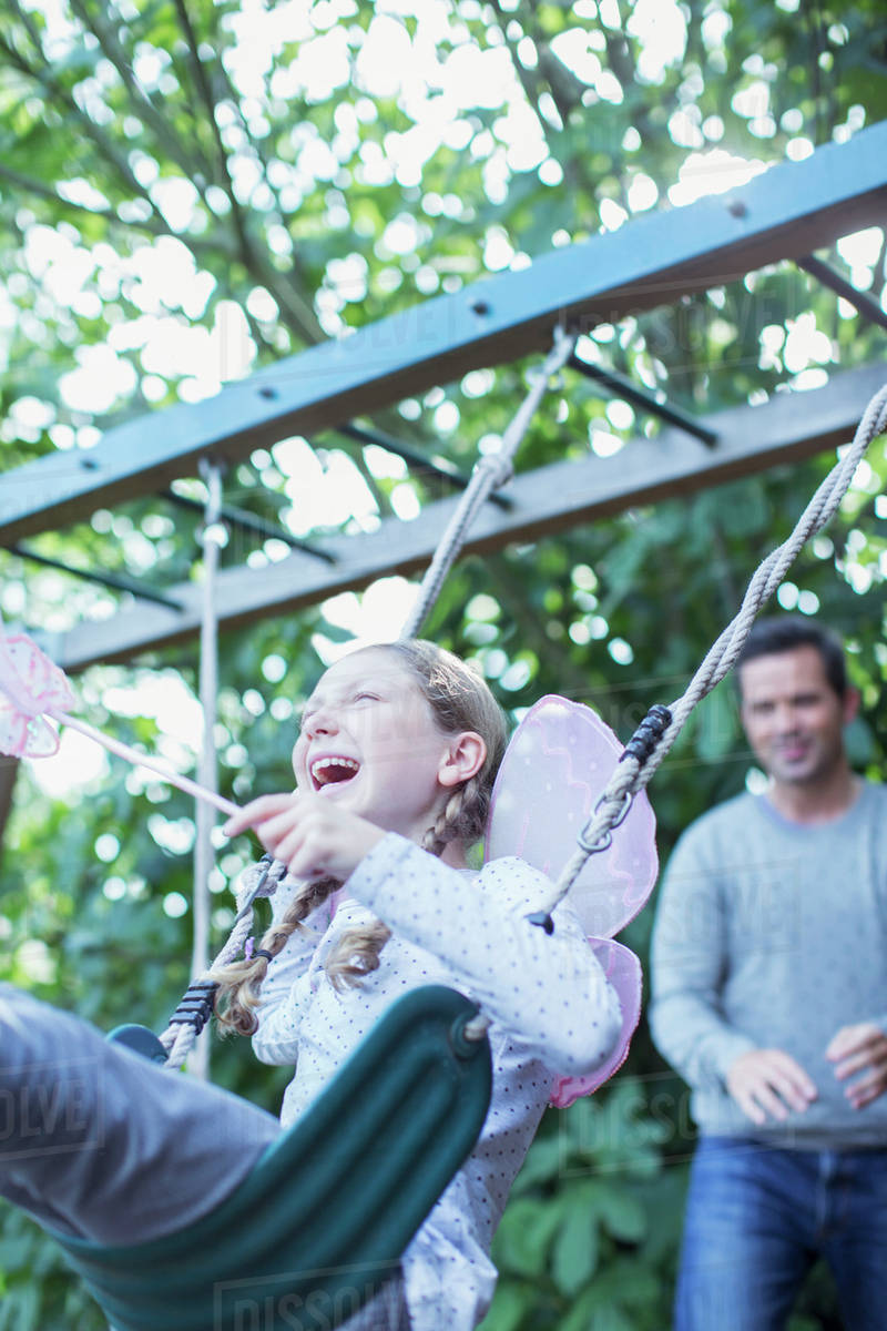 Father pushing daughter on swing outdoors Royalty-free stock photo