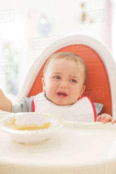 Baby boy crying in high chair Royalty-free stock photo