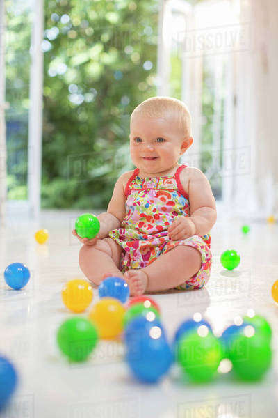 Baby girl playing with toys on floor Royalty-free stock photo