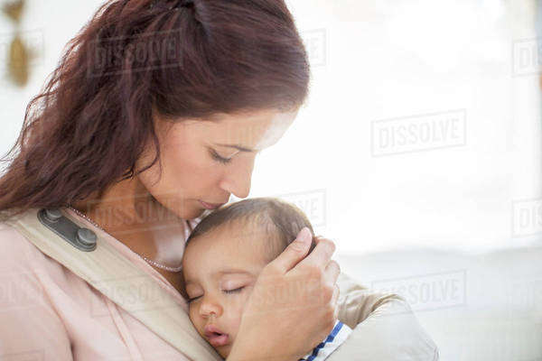 Mother kissing sleeping baby girl Royalty-free stock photo
