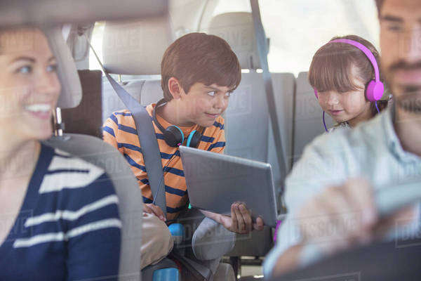 Brother and sister sharing digital tablet in back seat of car Royalty-free stock photo