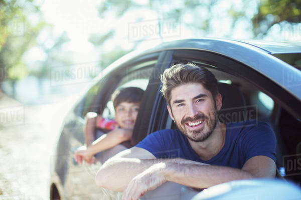 Portrait of smiling father and son leaning out car windows Royalty-free stock photo